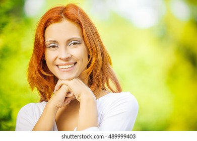 Portrait of beautiful young redhead woman wearing white blouse at summer green park.
