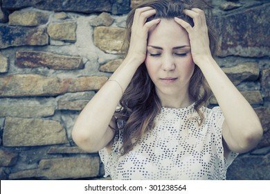 portrait of a beautiful young sad girl standing near the wall outdoors at the day time