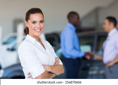 portrait of beautiful young saleswoman standing inside vehicle showroom