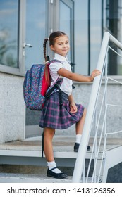 Portrait of beautiful young schoolgirl with backpack near school
