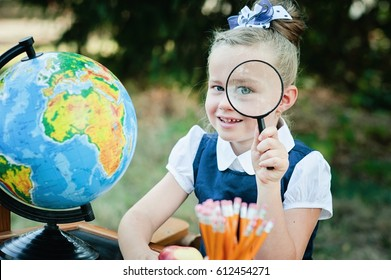 Portrait of a beautiful young Schoolgirl looking through a magnifying glass and sitting at a desk on the background autumn park. day of knowledge. beginning of the school year. school equipment