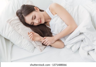 Portrait of beautiful young sexy asian woman with attractive smile enjoy fresh soft bedding linen mattress in white bed room modern apartment. Cute asia girl sleep resting, good night sleep concept.