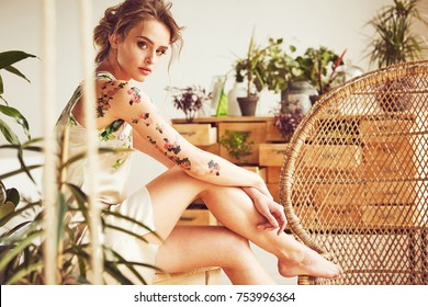 Portrait of beautiful young sexy woman with updo hairstyle and flower tattoos on her arms and shoulders wearing silk floral dress in studio with plants and straw chair