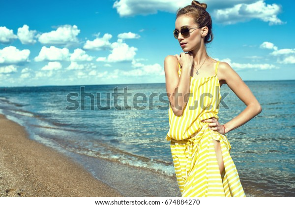 Portrait of a beautiful young slim woman with updo hair wearing yellow striped baggy summer dress with side slit and round mirrored sunglasses standing at the seaside and looking aside. Copy space
