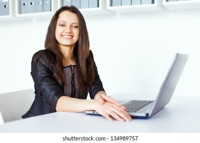 Portrait of beautiful young smiling brunette business woman working on a laptop in office