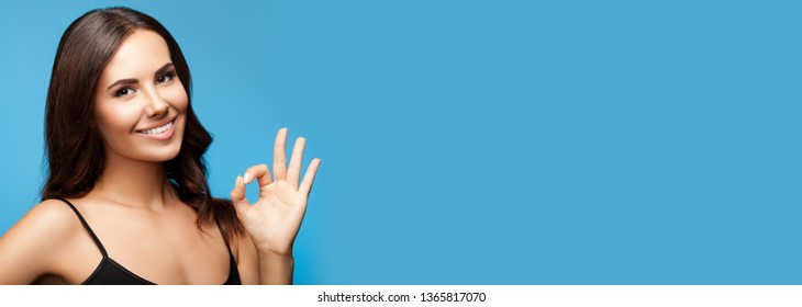 Portrait of beautiful young smiling brunette woman showing okay gesture, on blue background, with big copy space area, for some text, advertising or slogan