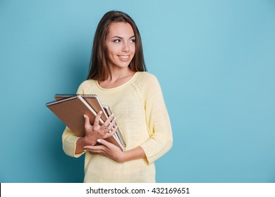 Portrait of beautiful young smiling brunette holding notebooks isolated on the blue background