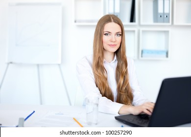 Portrait of beautiful young smiling business woman working on a laptop at bright office