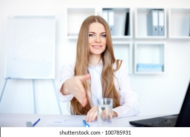 Portrait of beautiful young smiling business woman sitting at desk offering a handshake in bright office