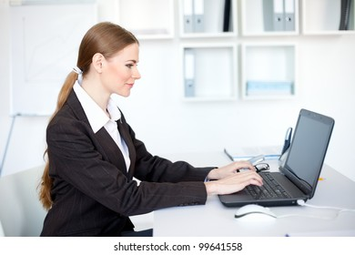 Portrait of beautiful young smiling business woman working on a laptop at office