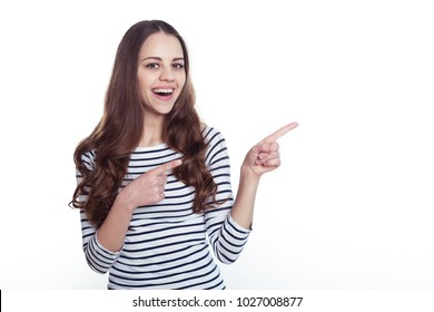 Portrait of a beautiful young smiling modern woman in casual clothes who points her fingers at something.