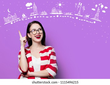 portrait of the beautiful young smiling woman with travel route on the violet background