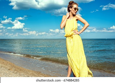 Portrait of a beautiful young smiling woman with updo hair wearing long yellow striped baggy summer dress and round mirrored sunglasses walking along the seaside and looking aside. Copy space