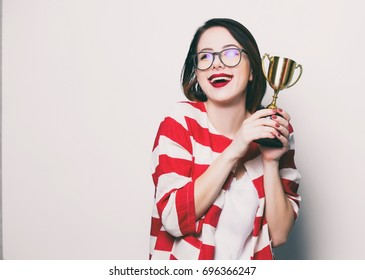 portrait of the beautiful young smiling woman with cup trophy