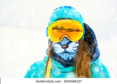 Portrait of beautiful young snowboarder girl in snowboard goggles.