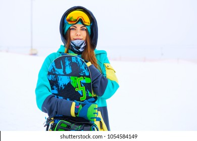 Portrait of beautiful young snowboarder girl holding snowboard.