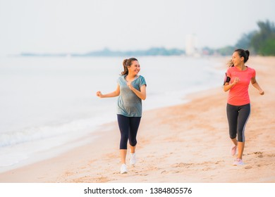 Portrait beautiful young sport asian woman running and exercise on the beach near sea and ocean at sunrise or sunset time for healthy concept