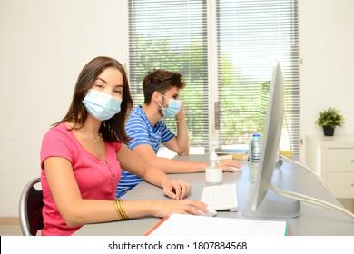 Porträt eines schönen jungen Schülers im Schulunterricht mit einem covid 19 chirurgischen Maske-Schutz