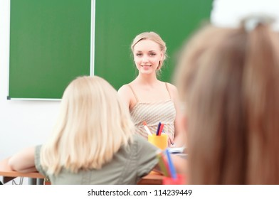 portrait of beautiful young teacher, sits at a desk in the classroom