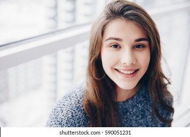 Portrait of a beautiful young teenager  girl with perfect skin setting near window