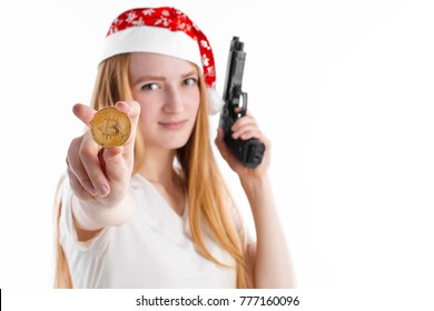 A portrait of beautiful young thief in red Santa cap holding black gun and showing golden bitcoin in camera isolated on white background. New Year and Christmas mood gangster with free copy space