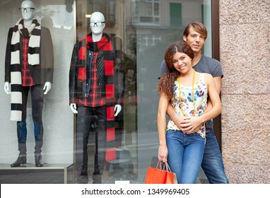 Portrait beautiful young tourist couple hugging by clothing fashion store manikins, carrying bags, shopping mall smiling outdoors. Man and woman consumers travel holiday, leisure recreation lifestyle.