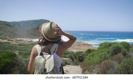 Portrait of a beautiful young tourist (girl), in a white dress, looks, with a backpack, in a straw hat, walking along rocks, sea background and mountains. Concept: recreation, beautiful view, sports.