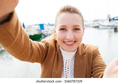 Portrait of beautiful young tourist woman visiting port, holding camera with hands taking selfies pictures, joyful smiling outdoors. Female using technology, networking leisure recreation lifestyle.