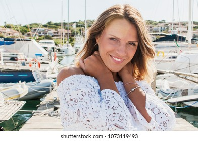 Portrait of beautiful young tourist woman in sunny harbor