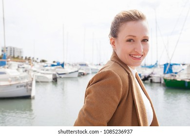 Portrait of beautiful young tourist woman visiting a yachting port on holiday, turning looking smiling at camera, joyful fun in outdoors coastal destination. Female travel adventure, leisure lifestyle