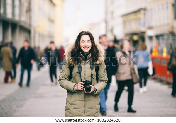 portrait Beautiful young tourist woman stands in the background of a crowd of people on a central street in Munich in Germany in winter. Holds a black big professional camera and smiles.