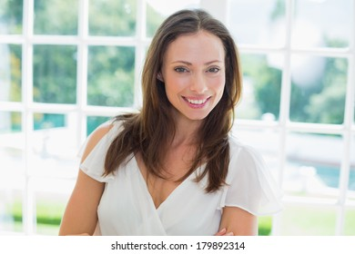 Portrait of a beautiful young woman against window in a bright home