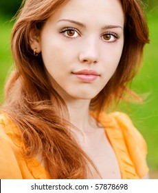 Portrait of beautiful young woman against green lawn.