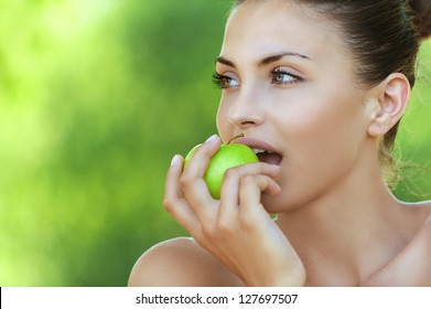 Portrait of beautiful young woman with apple, against background of summer green park.