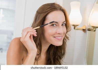 Portrait of a beautiful young woman applying mascara in the bathroom at home