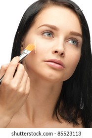 Portrait of beautiful young woman applying foundation on her face
