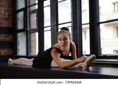Portrait of beautiful young woman with athletic flexible body doing right split, sitting on wide windowsill, warming up legs before ballet training, Flexibility, dancing, fitness and art concept