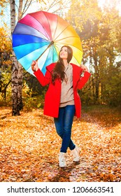 A portrait of a beautiful young woman in an autumn forest with bright and colorful umbrella. Lifestyle, autumn fashion, beauty.