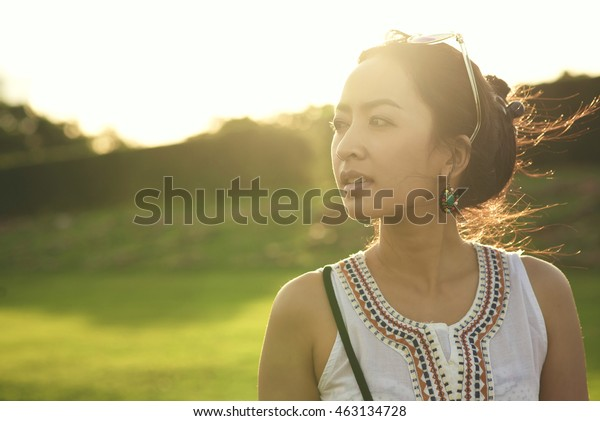 Portrait of Beautiful Young Woman Backlit at Sunset Outdoors. Soft warm sunny colors