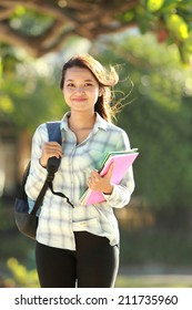 Portrait of beautiful young woman with bag and books walking in campus park