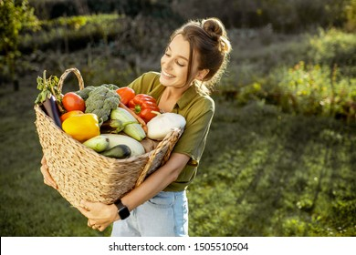 Portrait of a beautiful young woman with basket full of freshly picked up vegetables standing in the garden on a sunny evening