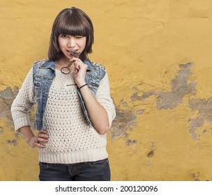 portrait of beautiful young woman biting a key