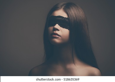Portrait of a beautiful young woman with a blindfold