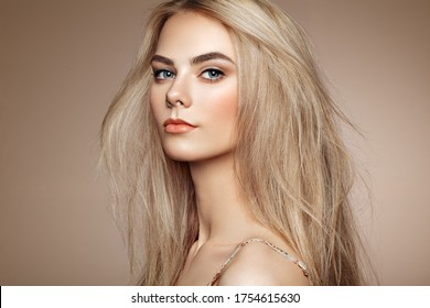 Portrait of beautiful young woman with blonde hair. Girl with long healthy and shiny smooth hair