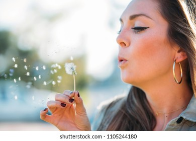 Portrait of a beautiful young woman blowing dandelion flower. Freedom and happiness concept.