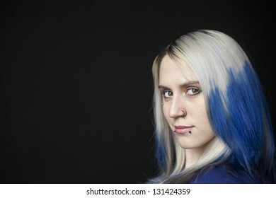 Portrait of a beautiful young woman with blue hair shot on a black background.