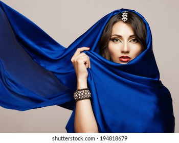 Portrait of a beautiful young woman in blue fabric