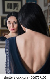 Portrait of beautiful young woman in blue dress with naked back, standing in front of the mirror, beauty fashion concept
