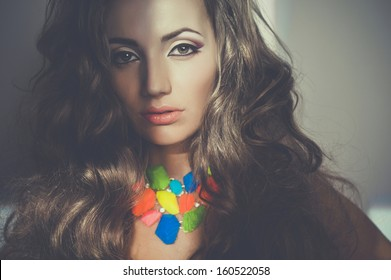 Portrait of beautiful young woman with bright necklace