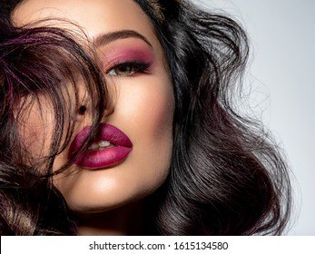 Portrait of beautiful young woman with bright maroon makeup. Beautiful brunette with bright cherry lipstick on her lips. Pretty girl with long black hair. Sexy girl